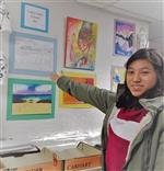 Kelly Garcia pointing to her artwork