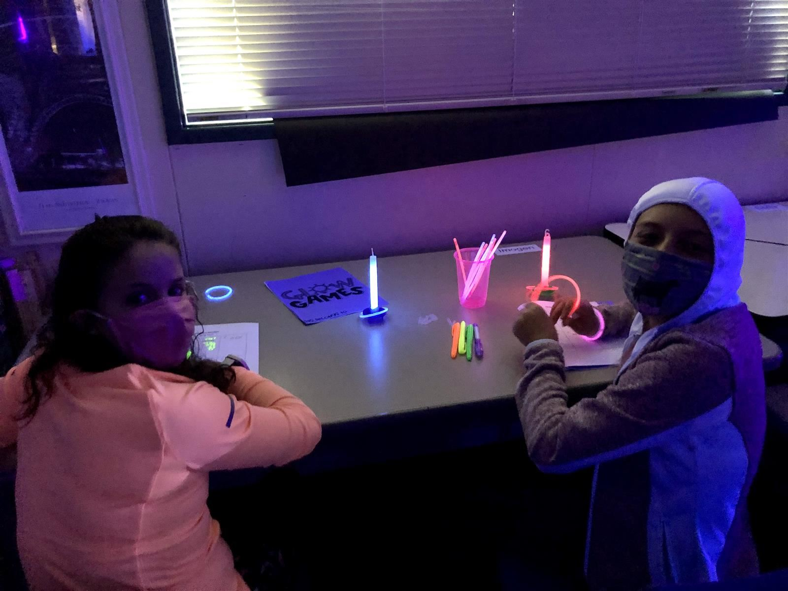 Two students at a desk doing glow-in-the dark math