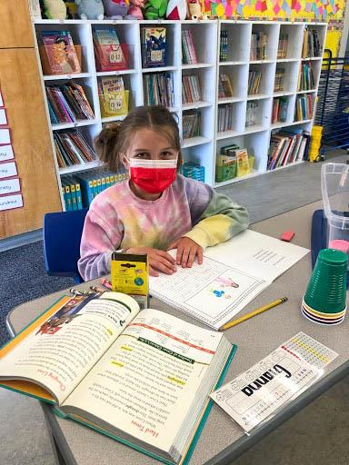 Elementary student wearing a mask while sitting at a desk in a classroom working on a writing assignment with a book open.