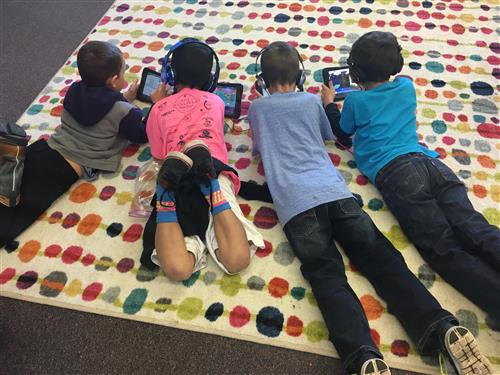 Students laying on ground on iPads